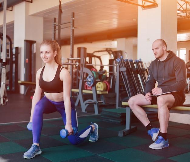 Instruktor Fitness Nadzoruje I Zapisuje W Zeszycie Wyniki Treningu Młodej Atletycznej Blondynki Wykonującej ćwiczenia Z Hantlami W Rękach Na Siłowni Premium Zdjęcia