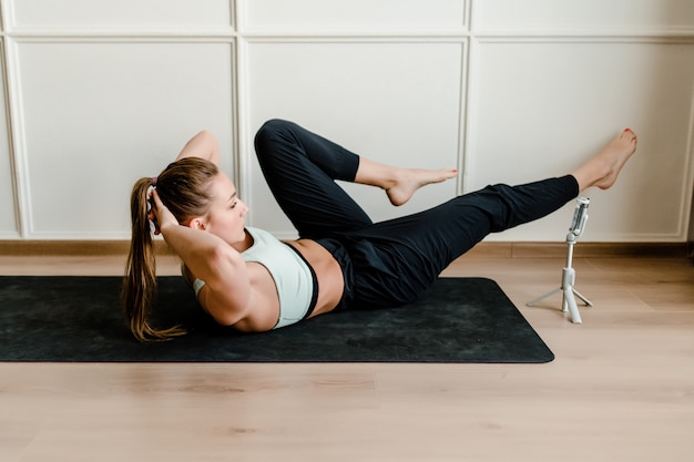 Instruktor fitness nagrywa na żywo trening sportowy na telefonie dla klientów internetowych w domu