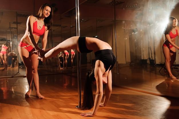 Instruktor fitness pole pole pomaga uczniowi zrobić pozę.