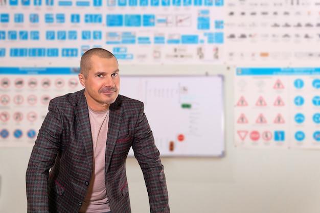 Instruktor jazdy mężczyzna uczy teorii na rozmytym tle sali szkoleniowej z obrazami znaków drogowych