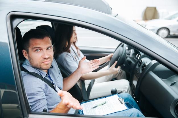 Instruktor jazdy wzrusza ramionami. mężczyzna nie rozumie, co robi jego studentka. atrakcyjna niewyraźna kobieta siedzi na fotelu kierowcy, trzyma koło i próbuje się skoncentrować