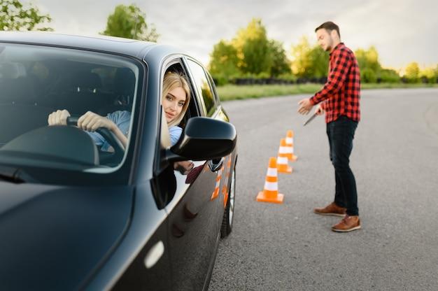 Instruktor jest zadowolony z jazdy swojej uczennicy między pachołkami, lekcja w szkole nauki jazdy. człowiek uczy pani. edukacja na prawo jazdy
