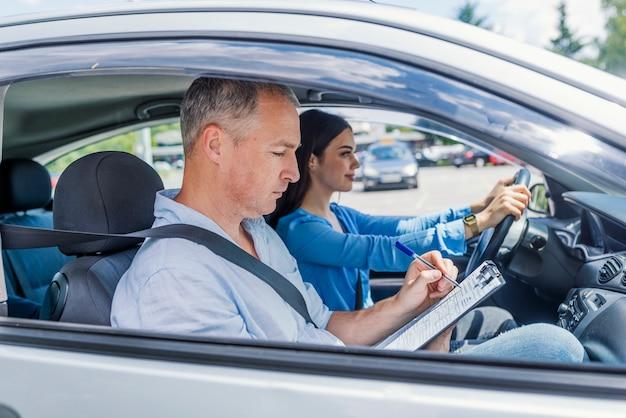 Instruktor nauki jazdy i studentka w samochodzie egzaminacyjnym