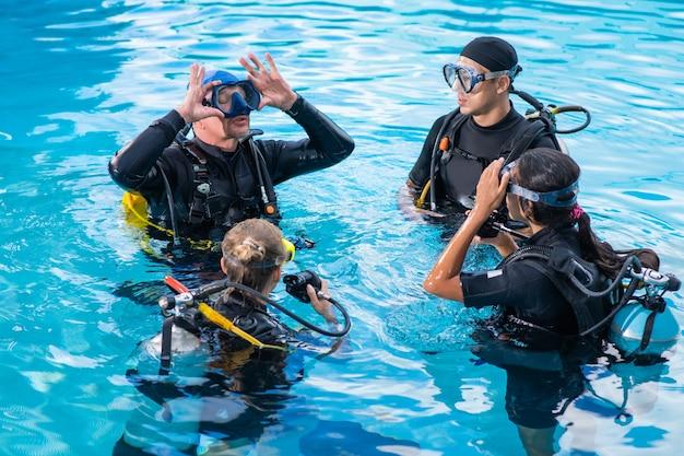 Instruktor nurkowania uczy, jak założyć maskę dla kursantów