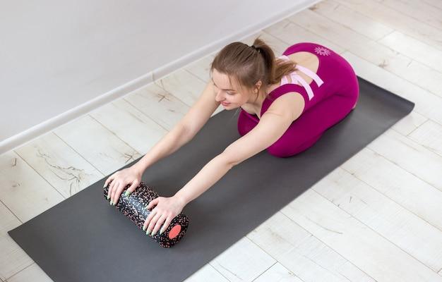 Instruktor pilates piękna kobieta, rozciąganie i rozgrzewanie za pomocą wałka z pianki, ćwiczenie, noszenie różowej odzieży sportowej, z bliska. koncepcja sportu i zdrowego aktywnego stylu życia.