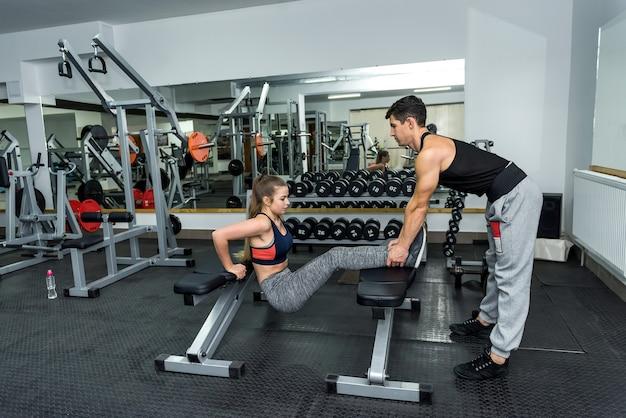 Instruktor pomaga młodej kobiecie robić ćwiczenia w siłowni