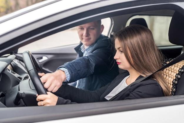 Instruktor pomaga młodej kobiecie w prowadzeniu samochodu