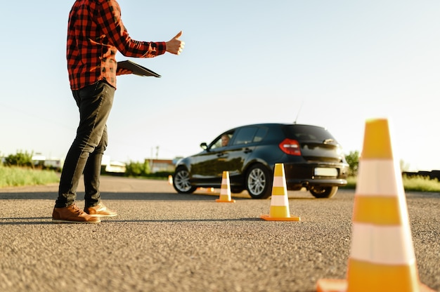 Instruktor pomaga studentce jeździć między pachołkami, lekcja w szkole nauki jazdy.