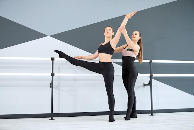 Instruktor pomagający dziewczynie w nauce ruchu choreograficznego