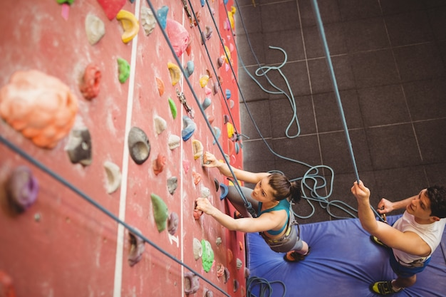 Instruktor prowadząca kobieta na wspinaczkowej ścianie