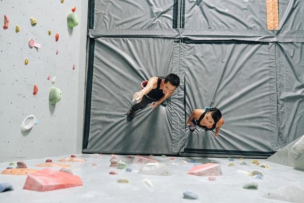 Instruktor ścianki wspinaczkowej wyjaśniający młodej kobiecie sposób wspinania się po ściance bulderowej, widok z góry