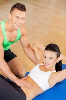 Instruktor szkolenia. kobieta trenująca na siłowni z osobistym trenerem