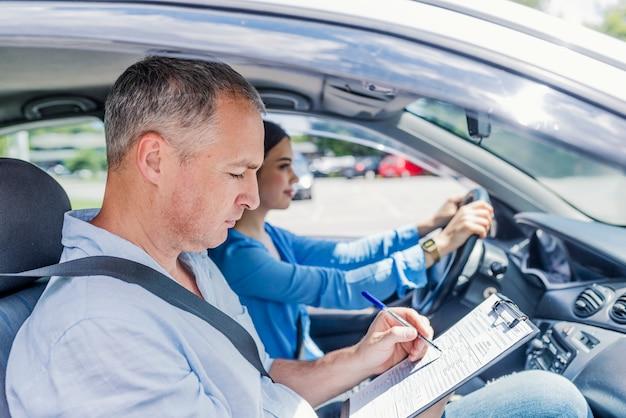 Instruktor szkoły jazdy daje egzamin podczas siedzenia w samochodzie.