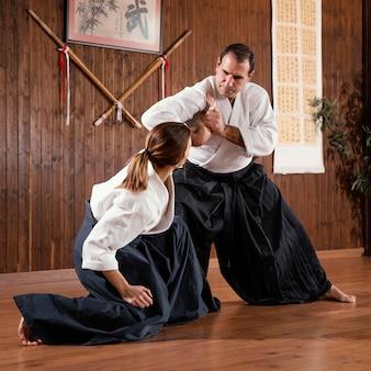 Instruktor sztuk walki mężczyzn trenujący ze studentem w sali treningowej