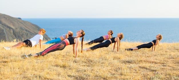 Instruktor trenuje dzieci jogi w górach nad oceanem.