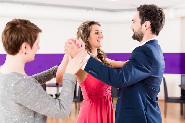 Instruktor w szkole tańca z parą mężczyzny i kobiety