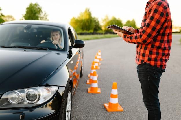 Instruktor z listą kontrolną i kobietą w samochodzie, egzamin lub lekcja w szkole jazdy. człowiek uczy pani prowadzić pojazd, egzamin. edukacja na prawo jazdy
