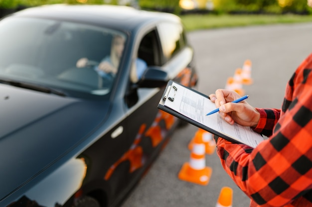 Instruktor z listą kontrolną i kobieta w samochodzie, egzamin lub lekcja w szkole nauki jazdy.