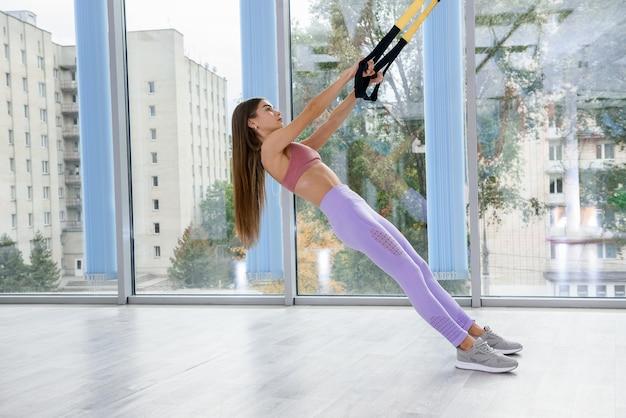 Instruktorka pokazująca rękę do ćwiczeń robi miejski trening na ramiona i klatkę piersiową z paskami fitness trx. pojęcie zdrowego stylu życia