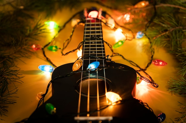 Instrument muzyczny na ciemnym tle. gitara elektryczna z podświetlaną girlandą na ciemnym tle. klasyczne kształty gitary prezentowej na boże narodzenie, nowy rok. muzyka noworoczna i bożonarodzeniowa, koncepcja
