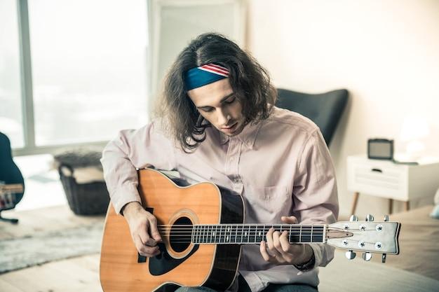 Instrument osobisty. skupiony ciemnowłosy facet pokazujący swoje doskonałe umiejętności podczas gry na gitarze akustycznej