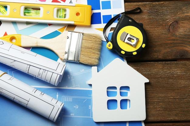 Instrumenty budowlane, plan i pędzle na drewnianym stole