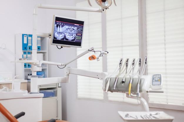 Instrumenty i narzędzia stomatologiczne w gabinecie stomatologicznym. gabinet stomatologiczny, w którym nikogo nie ma i pomarańczowy sprzęt do leczenia jamy ustnej.