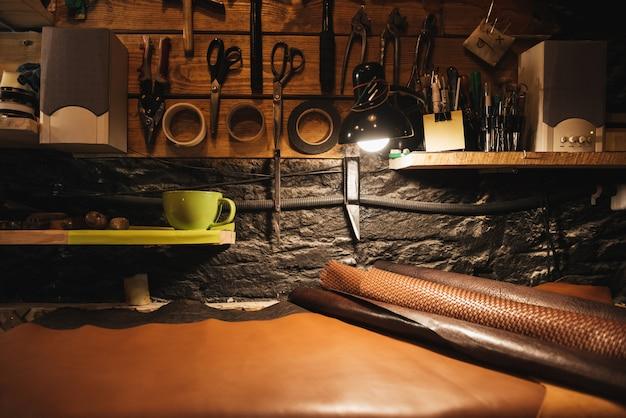 Instrumenty na drewnianej ścianie w warsztacie obuwniczym.