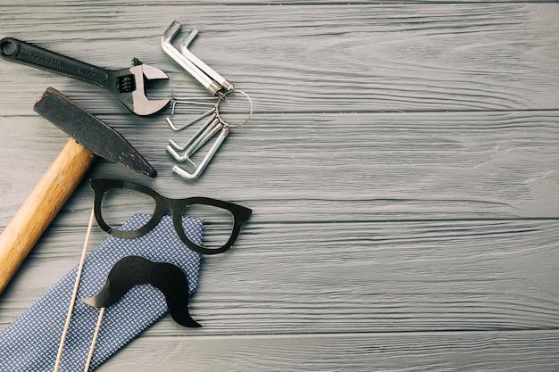 Instrumenty w pobliżu ozdobnych okularów i wąsów z krawatem