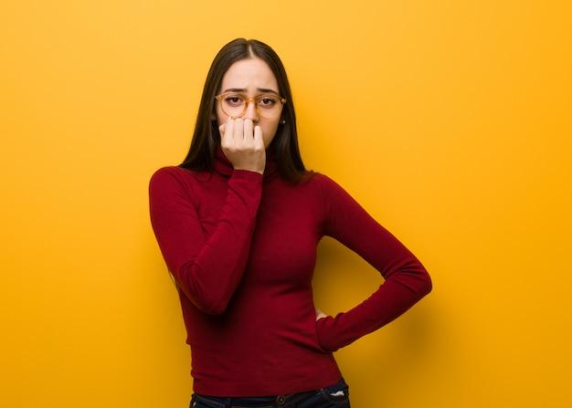 Intelektualna młoda dziewczyna gryząca paznokcie, nerwowa i bardzo niespokojna