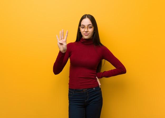 Intelektualna młoda dziewczyna pokazuje liczbę cztery