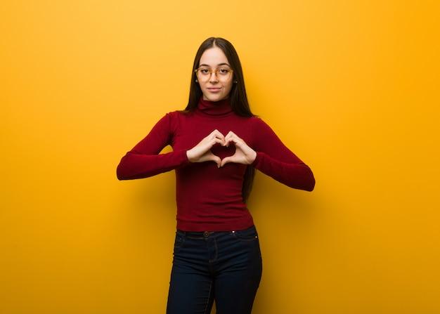 Intelektualna młoda dziewczyna robi kształtowi serce z rękami