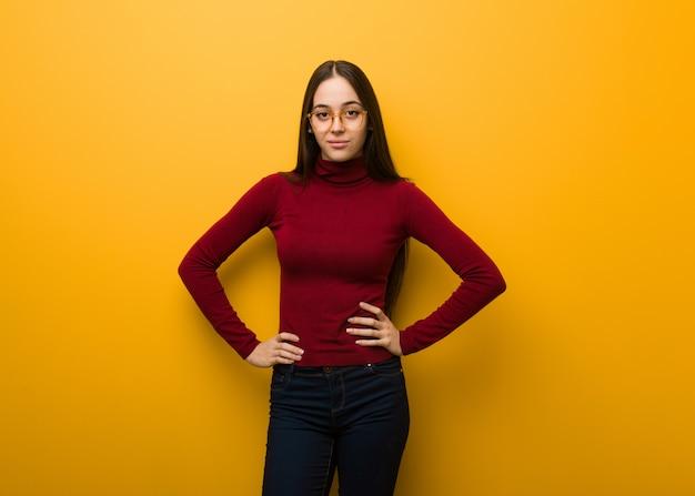 Intelektualna młoda dziewczyna z rękami na biodrach