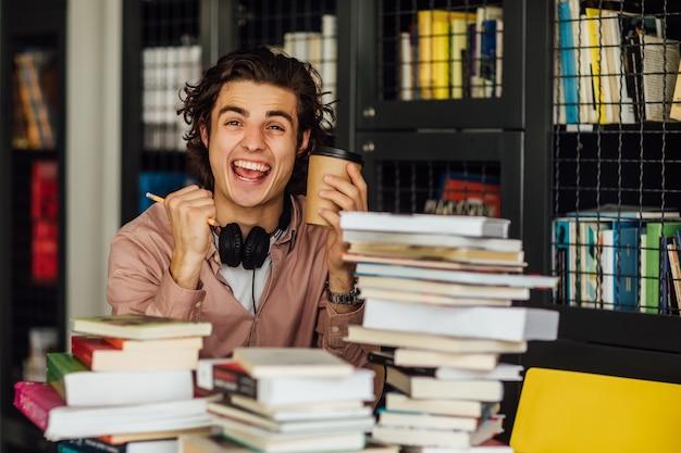 Intelektualny mężczyzna czytający książkę siedzący w bibliotece przed regałami z książkami z filiżanką kawy