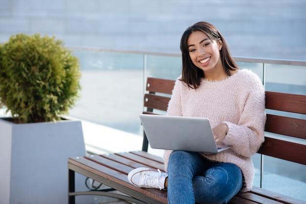 Inteligentna, aktywna dziewczyna wykorzystująca laptopa do wykonywania codziennych zadań i pracy z dowolnego miejsca, które lubi