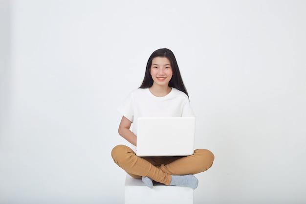 Inteligentna atrakcyjna młoda kobieta używa laptopa siedzącego ze skrzyżowanymi nogami na szarym tle studia