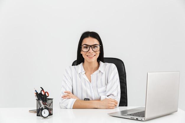 Inteligentna brunetka biznesmenka siedzi przy stole z papeterii i pracuje na laptopie w biurze odizolowane na białej ścianie