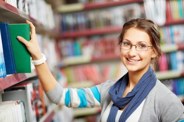 Inteligentna dziewczyna biorąc książkę z półki