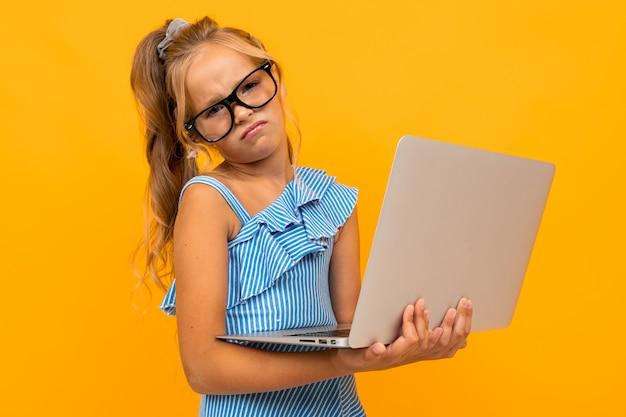 Inteligentna dziewczyna w okularach z laptopem na żółtej ścianie