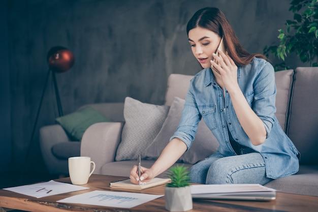 Inteligentna ekspertka od marketingu ma rozmowę telefoniczną, pisząc zeszyt