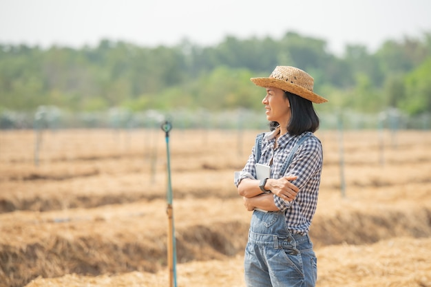 Inteligentna farma. piękna rolniczka używa tabletu do sterowania swoją farmą i biznesem z radością i uśmiechem. koncepcja biznesu i rolnictwa. rolnik lub agronom badają przygotowanie działki pod uprawę warzyw.