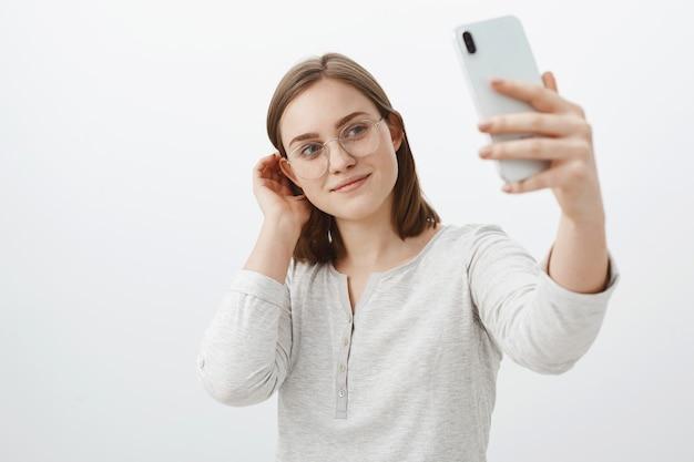 Inteligentna i czuła kobieta w okularach, strzepująca pasmo włosów za uchem i uśmiechająca się uroczo podczas robienia selfie na nowym smartfonie, pozująca na szarej ścianie, zadowolona z robienia postów w sieci społecznościowej