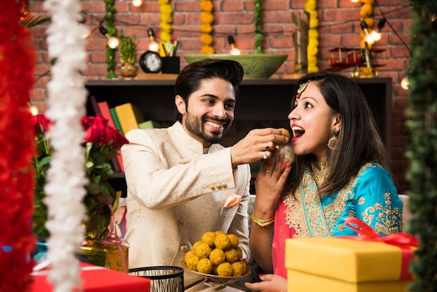 Inteligentna indyjska para je słodkie laddu na diwali lub rocznicę, selektywne skupienie