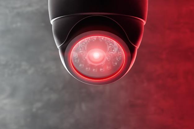 Inteligentna kamera cctv pod sufitem z czerwonymi światłami.