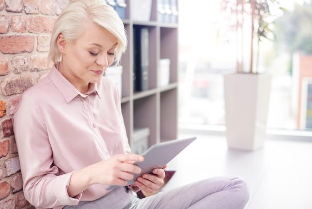 Inteligentna kobieta kucająca na podłodze i korzystająca z cyfrowego tabletu