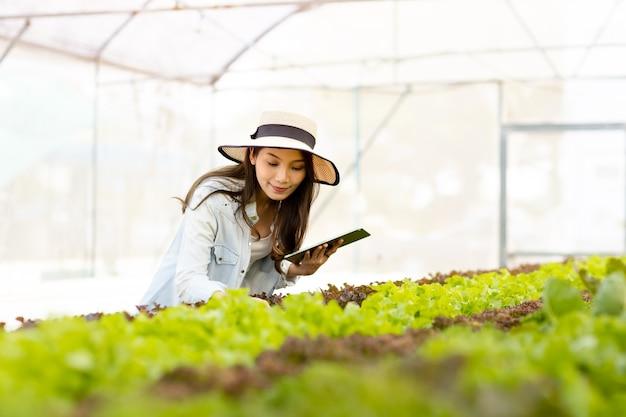 Inteligentna koncepcja technologii farmy i farmy. inteligentny młody azjatycki rolnik za pomocą tabletu sprawdza jakość i ilość organicznego hydroponicznego ogrodu warzywnego w szklarni.