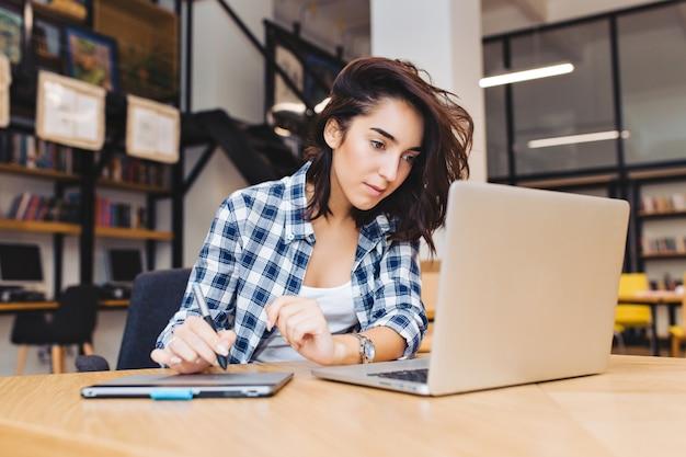 Inteligentna ładna młoda kobieta pracuje z laptopem na stole w bibliotece. studia na uniwersytecie, nauka, wolny strzelec, praca, wyszukiwanie w internecie, bystry student, pracowity.