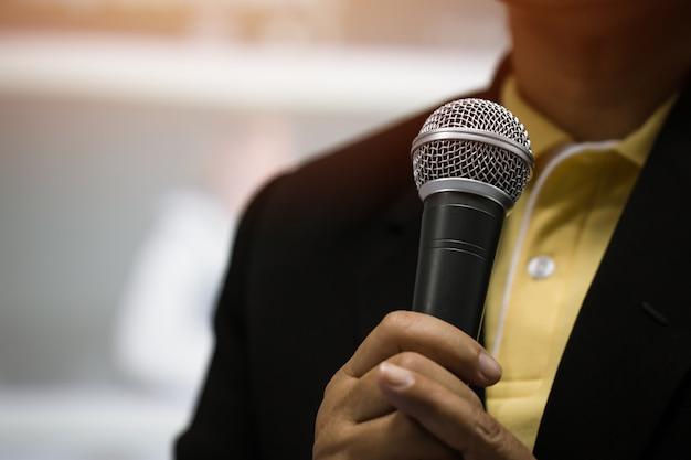 Inteligentna mowa biznesmena i mówienie z mikrofonami w sali seminaryjnej lub mówiące światło sali konferencyjnej z mikrofonem i przemówieniem. mowa jest wokalizowaną formą komunikacji ludzi.