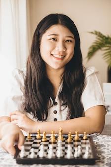 Inteligentna nastolatka chętnie gra w szachy w domu, aby trenować swój mózg i pamięć.