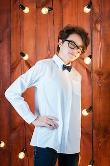 Inteligentna nastolatka w okularach pozuje w mieszkaniu na poddaszu nastolatka w białej koszuli na żarówkach...